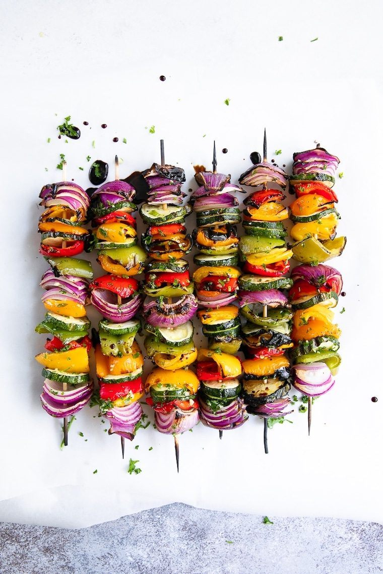 white surface with six colorful veggie skewers made with zucchini, bell pepper and onion