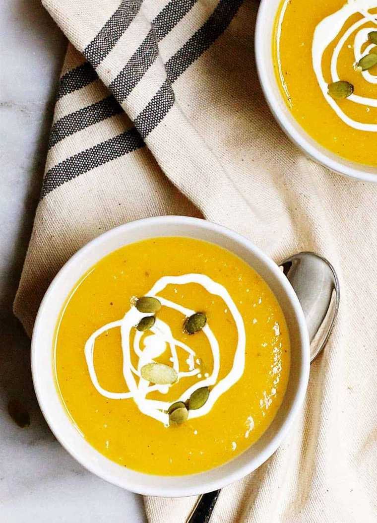 linen towel with two white bowls full of orange vegan butternut squash soup topped with seeds