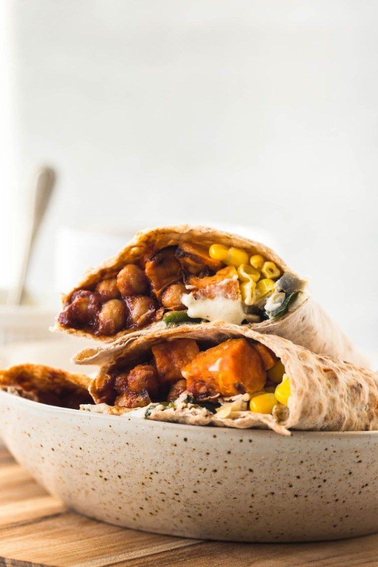 white speckled plate with two vegan wraps on it that are filled with sweet potato, chickpeas and corn