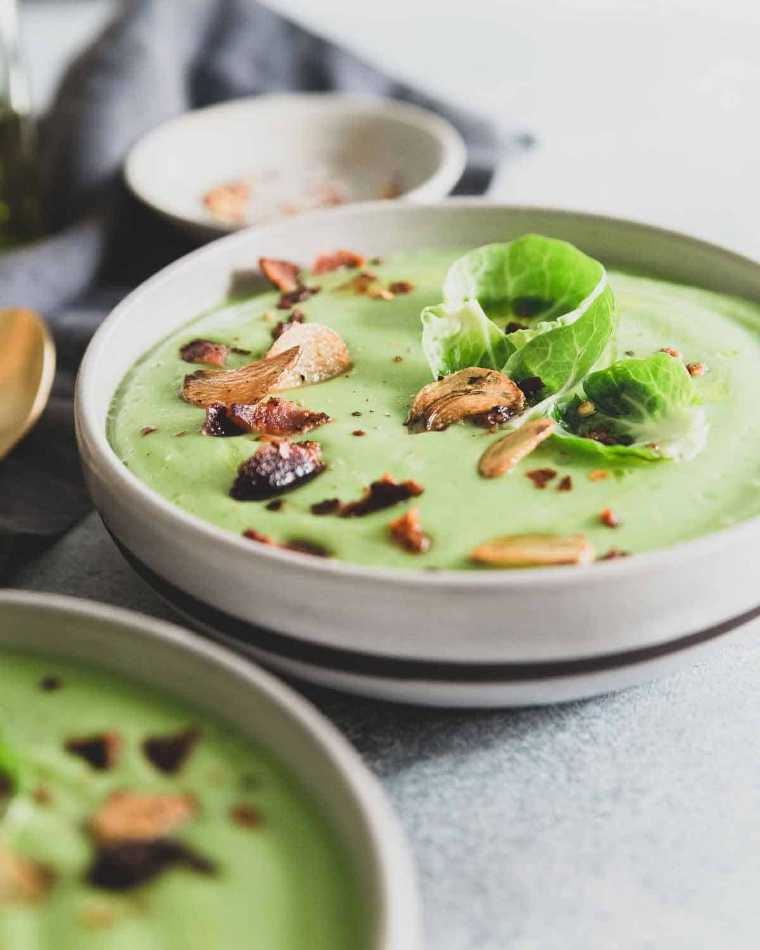 two white bowls with green brussels sprout soup topped with garlic