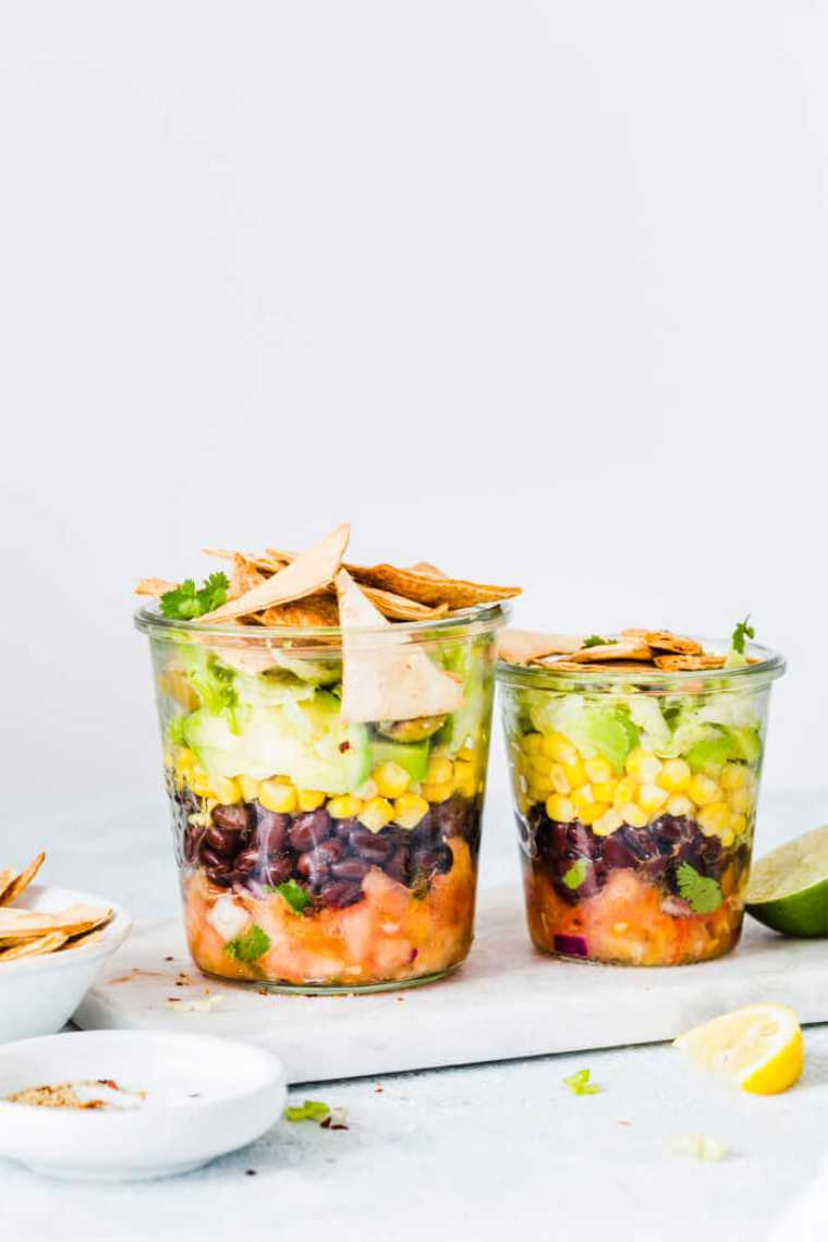 two glass jars with layered vegan mexican salad and tortillas