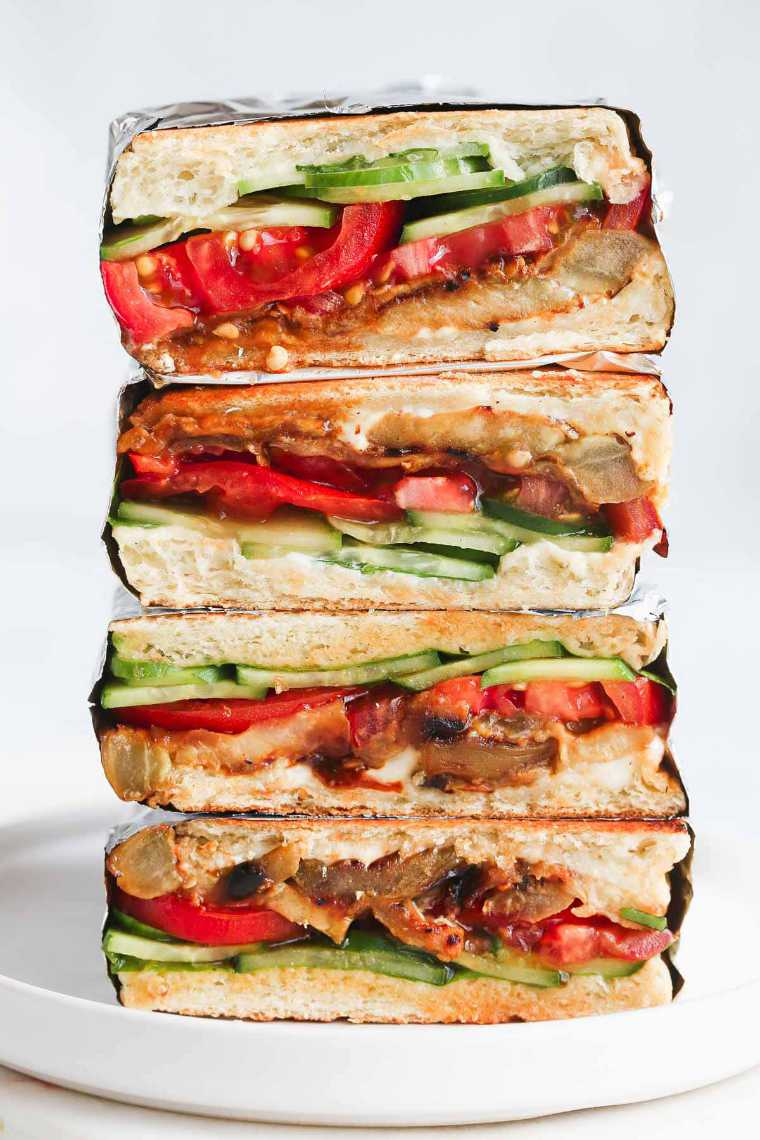 four vegan eggplant sandwiches with tomato and cucumber on top of each other as one of the best cold lunch ideas
