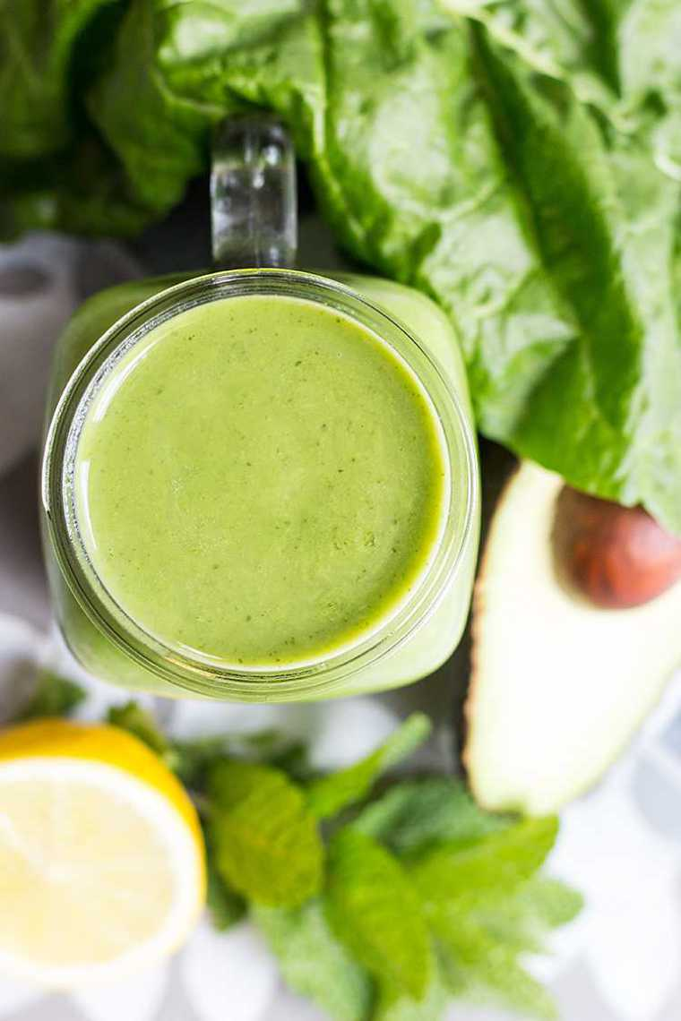 table with leafy greens, avocado, mint, lemon and a glass of green superfood smoothie