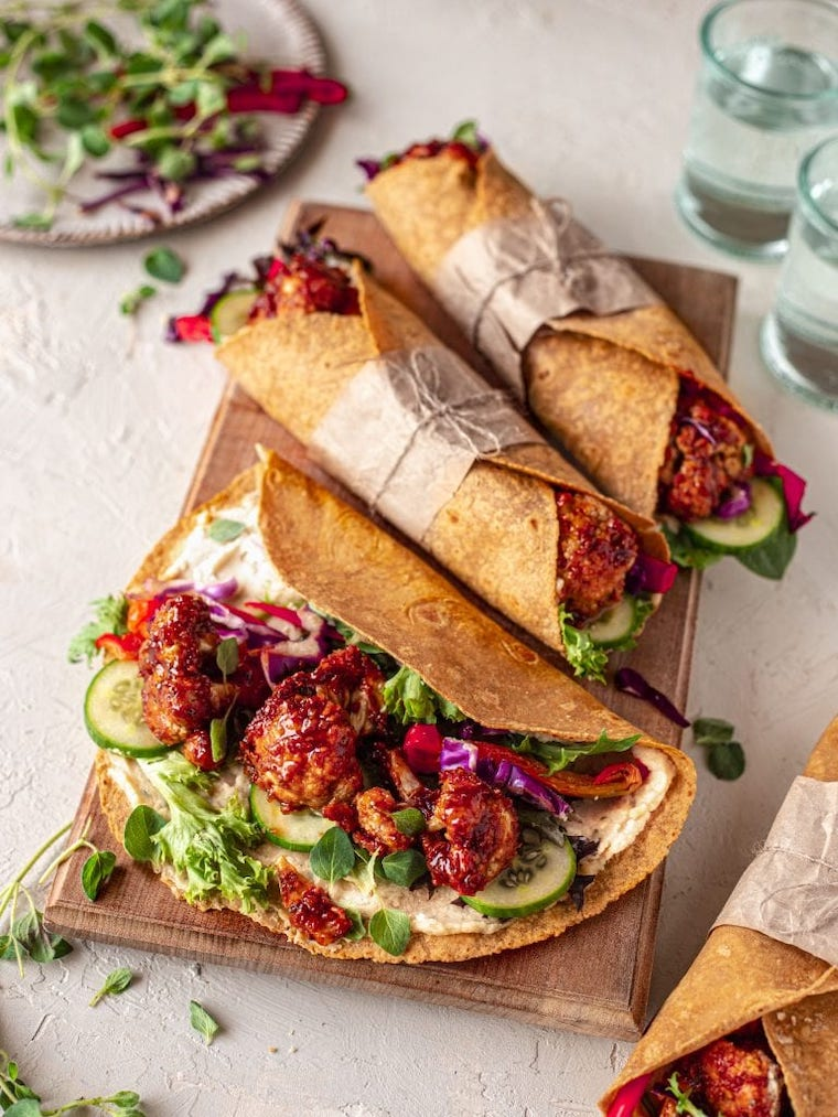 wooden chopping board with three sweet potato and bbq cauliflower wraps