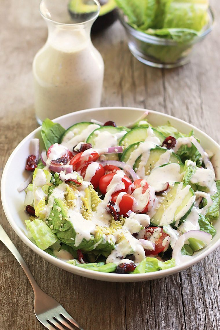 white bowl with mixed green salad drizzled with some white hemp seed oil free salad dressing