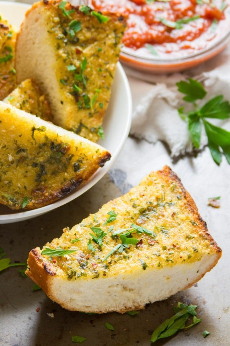 several slices of freshly baked vegan garlic bread with olive oil and herbs