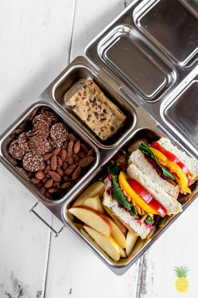 metal lunchbox containing almonds, energy balls, apple slices and a homemade rainbow veggie sandwich