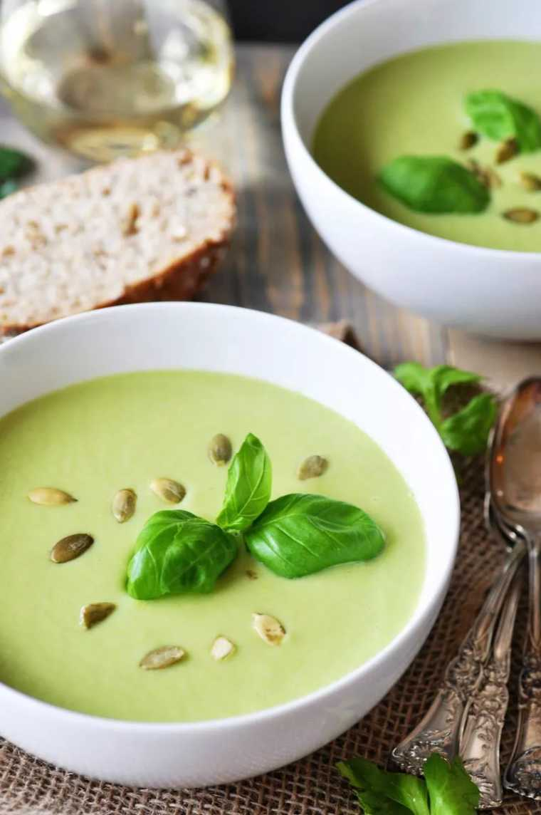 wooden table with a piece of bread and two white bowls filled with green vegan celery soup