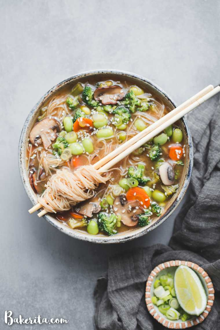 large bowl with vegetable miso noodle soup featuring broccoli, edamame, carrot and mushrooms