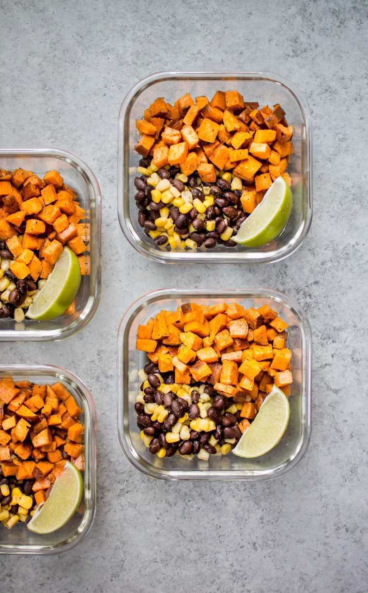 four glass containers with sweet potato cubes, black beans, corn and lime