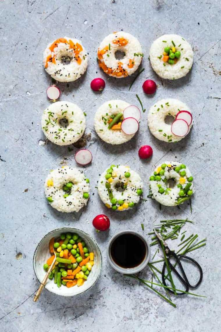 table with 9 rice-based sushi donuts made with different veggies