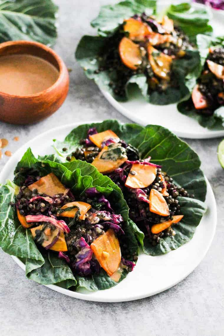 two white plates with collard wraps that are filled with black lentils and pumpkin