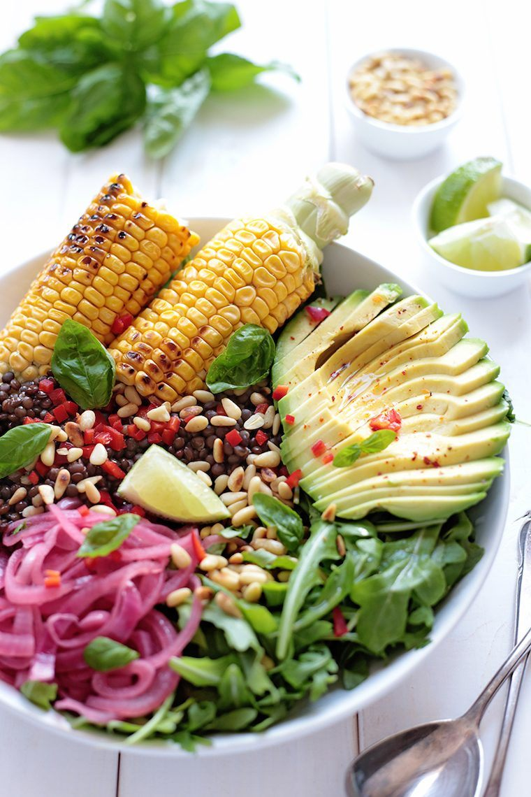 large white bowl with leafy greens, sliced avocado, pickled onion, lentils, grilled corn and pine nuts