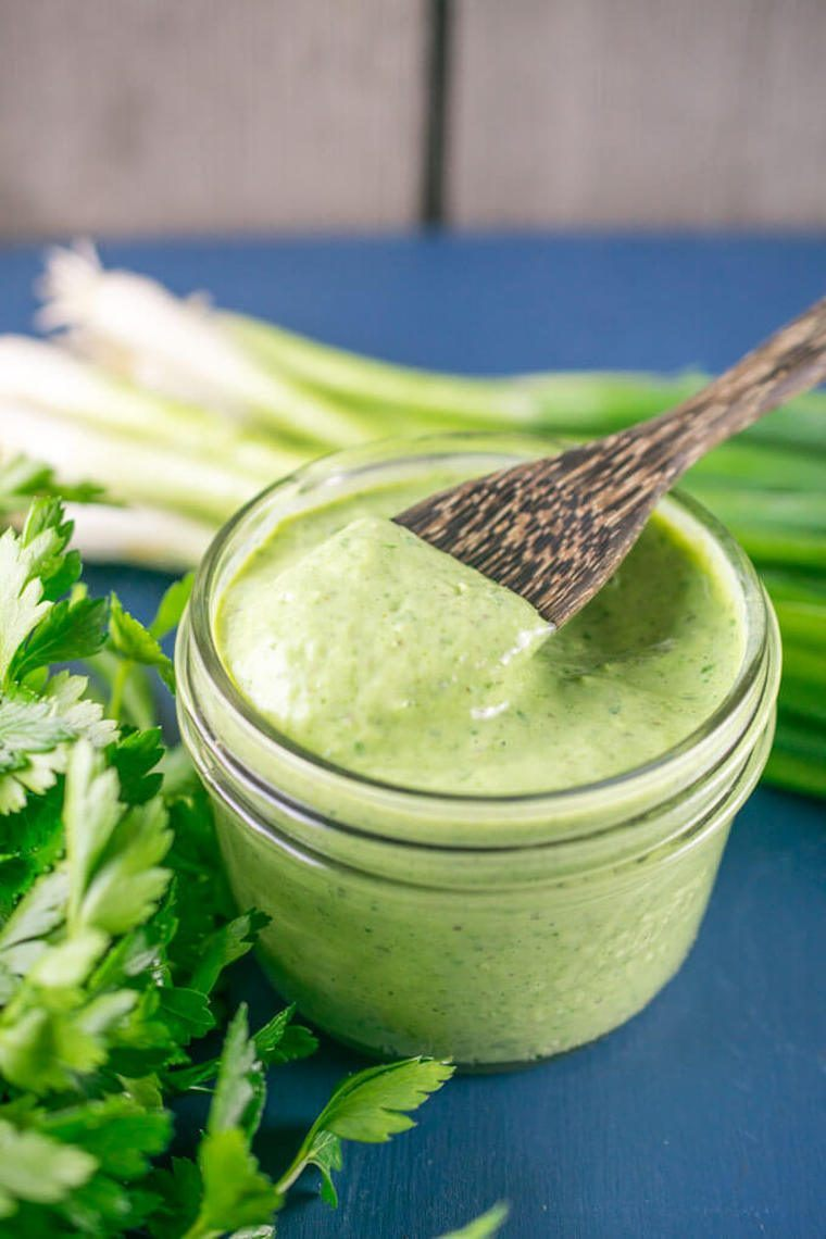glass jar with creamy green goddess dressing and a wooden spoon standing on a blue chopping board next to fresh herbs