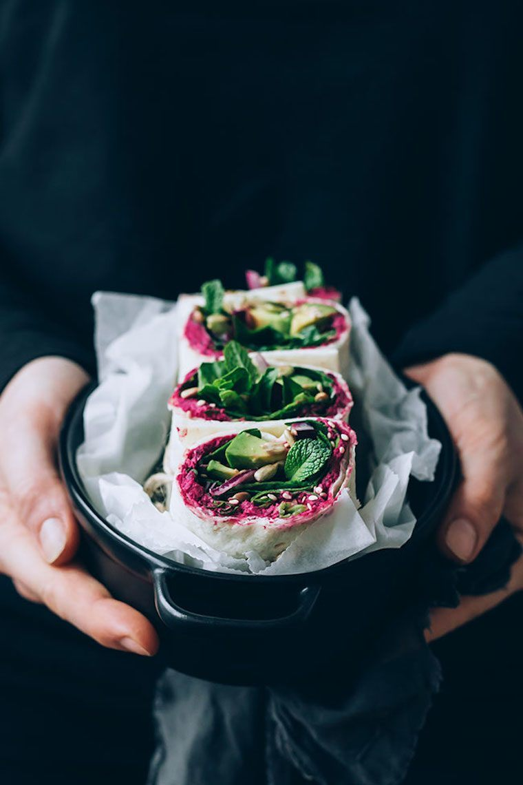 woman in black sweater holding a black baking dish with white parchment paper and four vegan beetroot hummus avocado wraps
