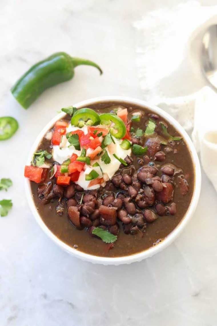 white table with a bowl of Instant Pot black bean soup topped with salsa and vegan yogurt
