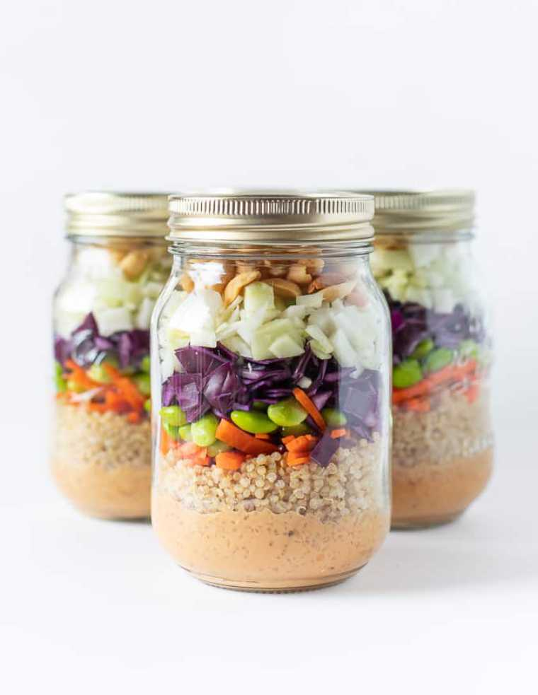 three mason jars with layered peanut crunch salad containing quinoa, edamame and red cabbage