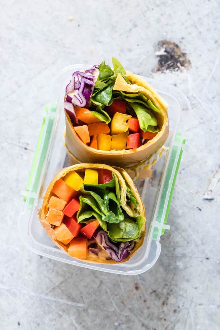 plastic food container with two colorful plant-based vegetable wraps