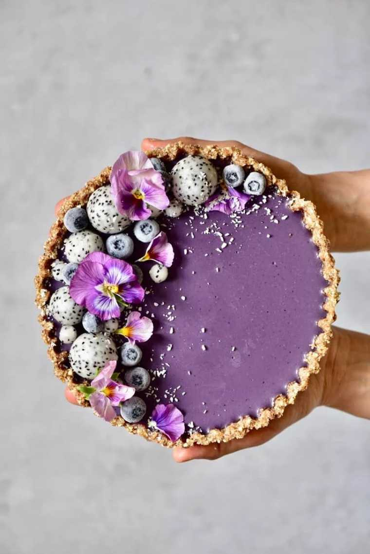 two hands holding a homemade raw vegan blueberry tart decorated with pitaya and edible flowers