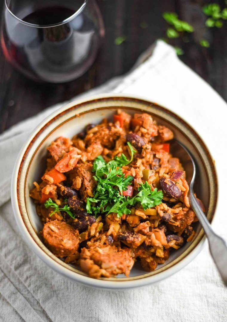 glass of red wine and a linen towel on which a bowl of hearty vegan jambalaya is placed