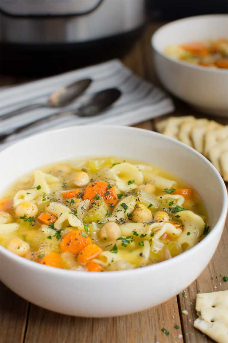 close up of a white bowl with vegan chickpea noodle soup and some crackers