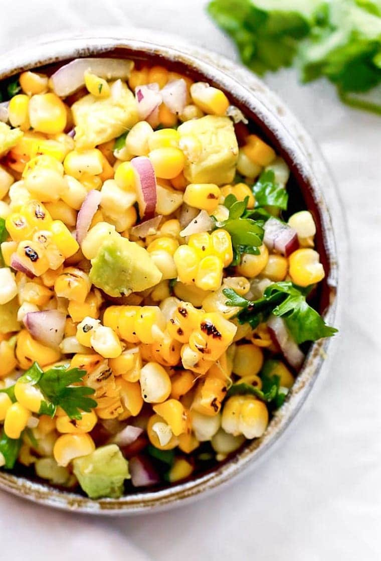close-up of bright bowl with corn, onion, avocado and fresh herbs