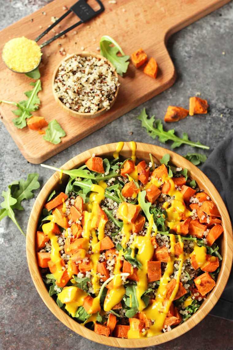 large wooden bowl with homemade quinoa, sweet potato arugula salad and mustard dressing