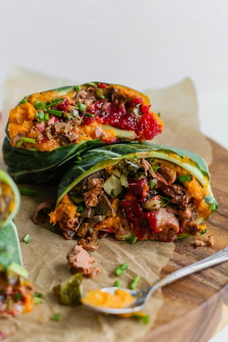 two colorfully stuffed vegan collard wraps on some parchment paper on a wooden chopping board