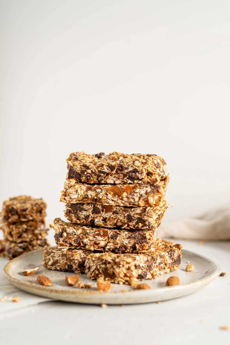 plate with six sliced no-bake vegan apricot granola bars stacked on top of each other
