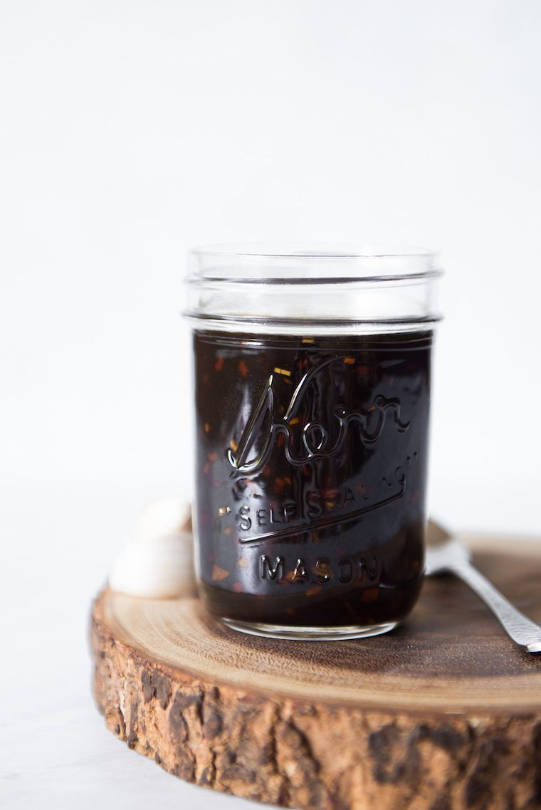 side view of a glass mason jar on a piece of wood containing dark brown homemade oil-free Teriyaki sauce
