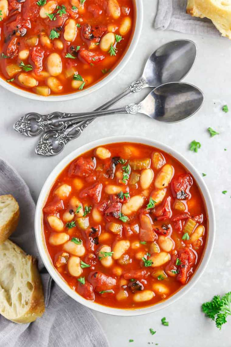 white table with two spoons, some bread and two bowls of plant-based tomato white bean soup