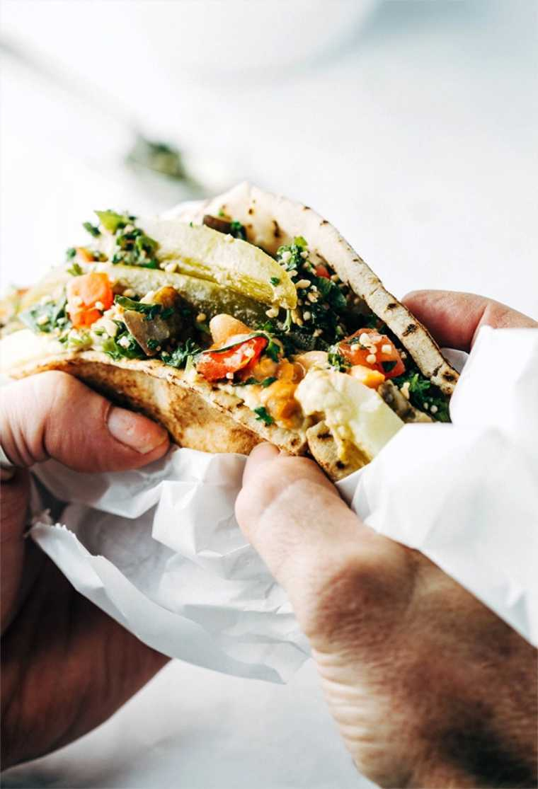 close up of two hands holding a homemade vegan sabich sandwich for lunch