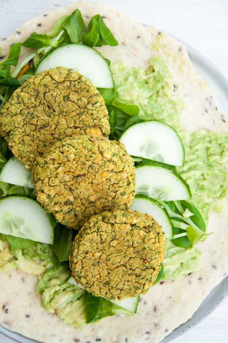 tortilla wrap on a white plate with avocado, lettuce, cucumber and spinach falafel