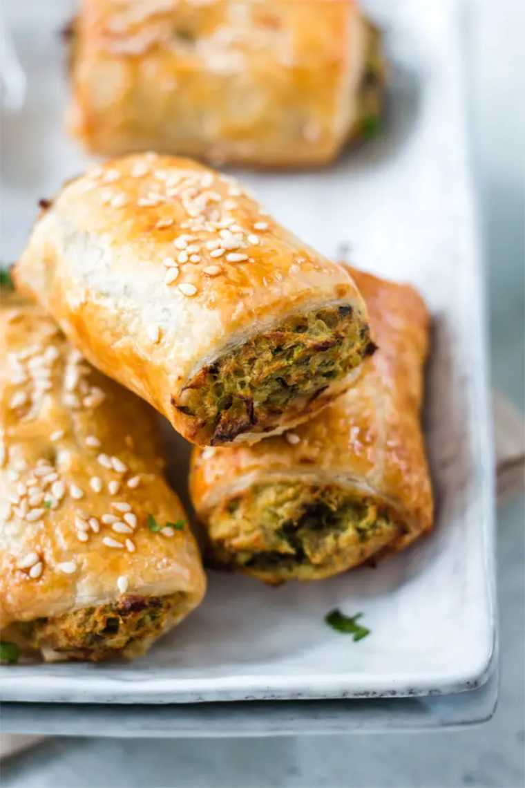 white plate with four homemade vegan sausage rolls containing vegetables