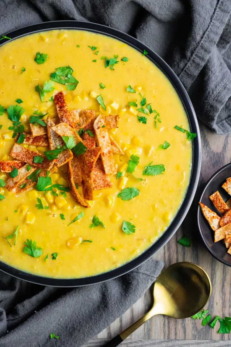 wooden table with a dark towel and a bowl of bright yellow vegan corn chowder