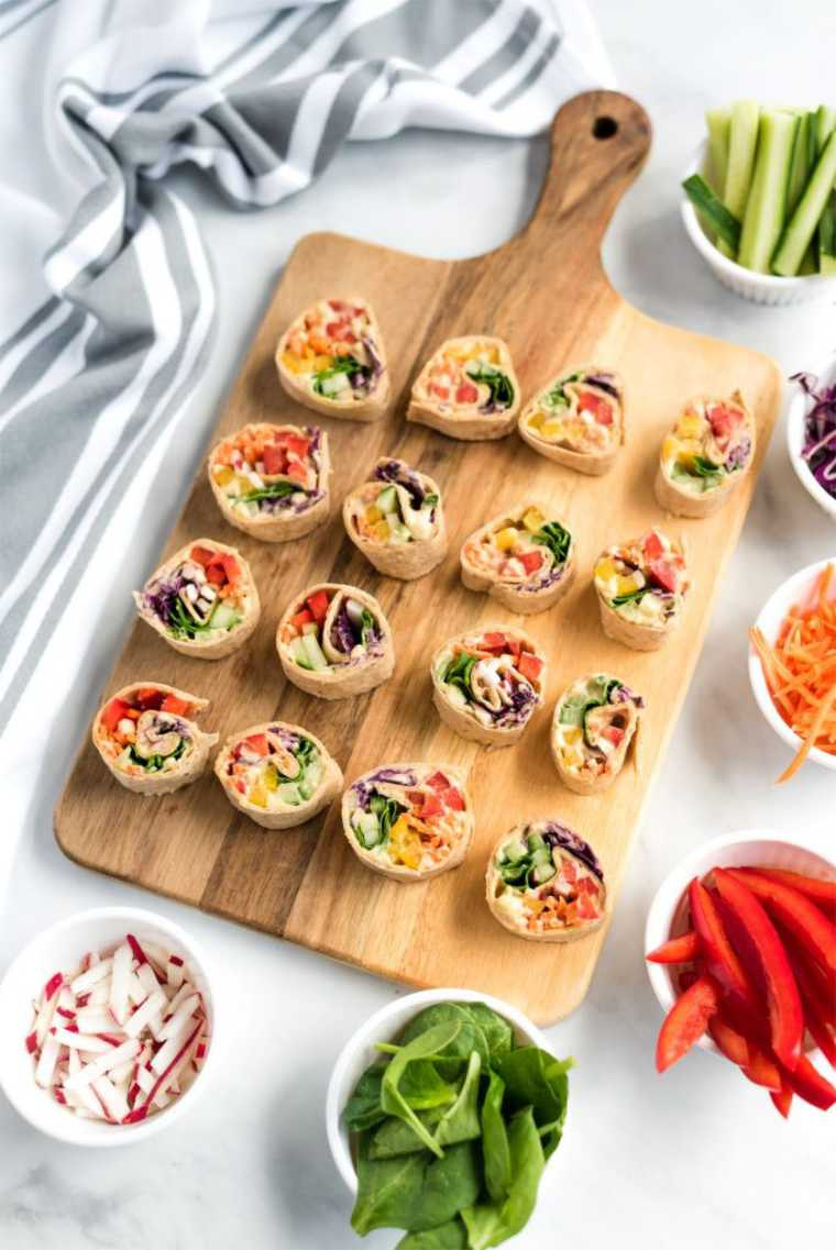 wooden chopping board with 16 small and colorful vegan vegetable pinwheels for a cold lunch