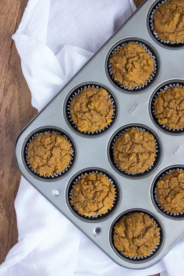 Vegan Pumpkin Muffins in tray standing on a white towel and wooden table