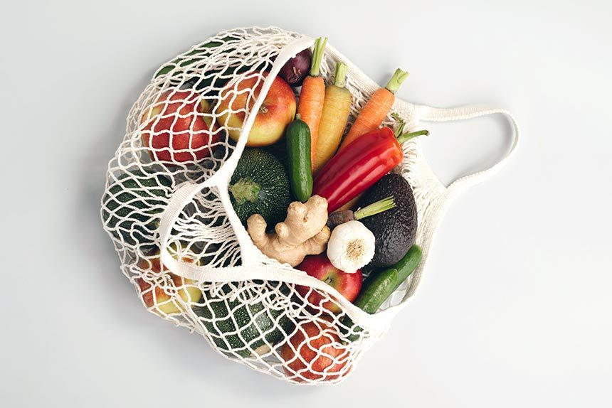 grocery bag filled with carrots, zucchini, avocado, apples, ginger and garlic