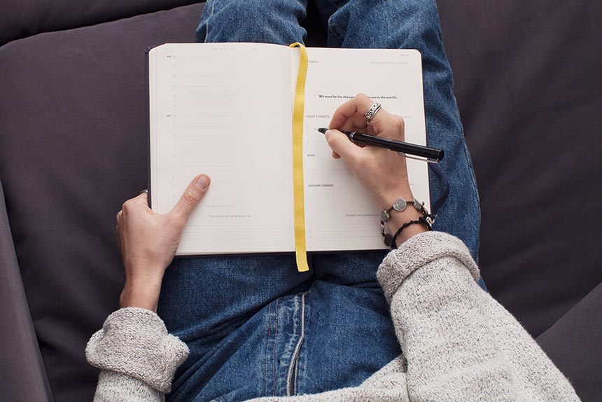 woman with cozy beige sweater and jeans sitting on the soda and writing in her journal