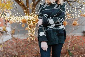 woman in black knitted sweater with white patterns standing in front of an autumn tree full of small lights during the holidays