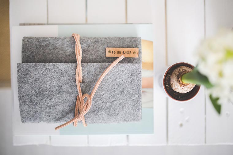 timer or planner covered in felt lying on a white wooden table next to a flower