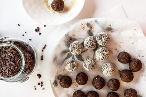 two kinds of vegan energy balls on parchment paper as vegan snack ideas next to some cacao nibs