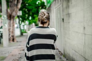 blonde woman from behind with a large woolen sweater walking through the streets