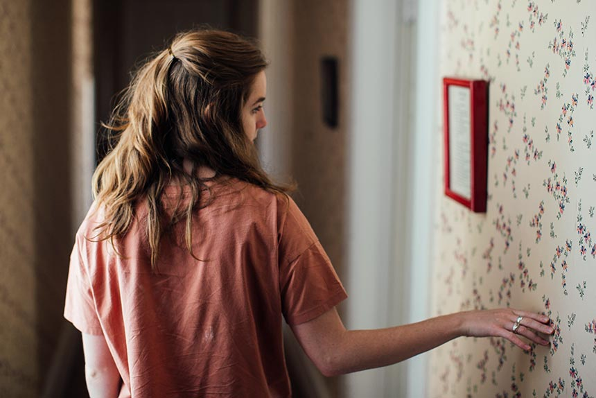 brown haired woman with rose shirt walking next to a flowery wallpaper along the hallway