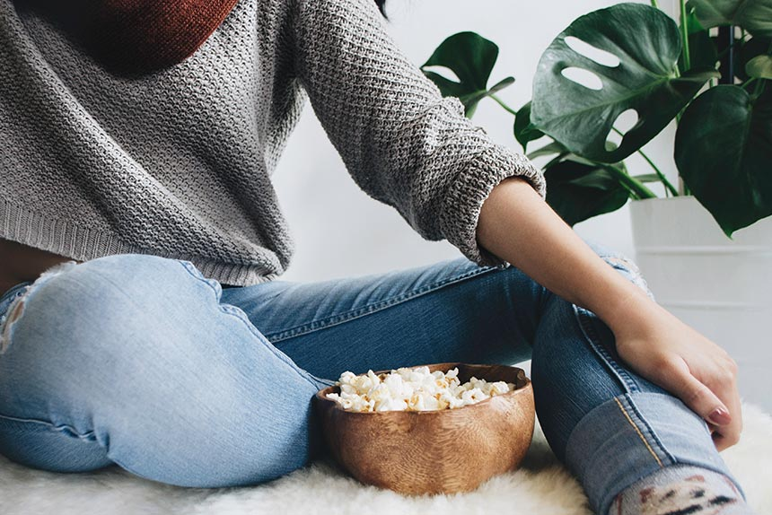 woman in tight jeans and grey knitted sweater sitting next to a wooden bowl of popcorn