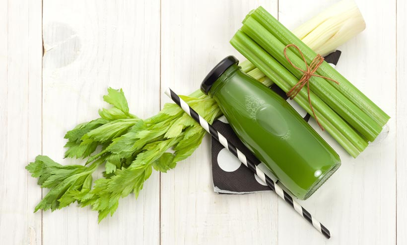 Top view of celery and small bottle of celery juice on a light wooden surface