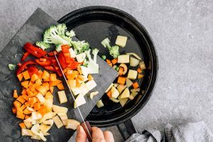 woman sauteing carrot, bell pepper and broccoli in a black pan with water instead of oil