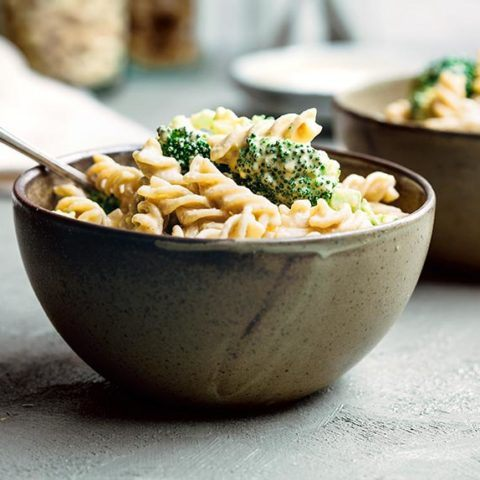 two bowls of vegan mac and cheese with broccoli standing on the counter