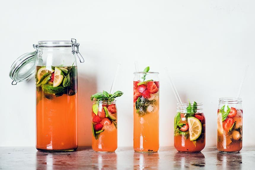 five glasses of different shapes and sizes filled with fruit-flavored and colored water next to each other