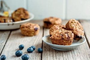 three vegan blueberry oat muffins on a small bright blue plate and wooden surface next to blueberries